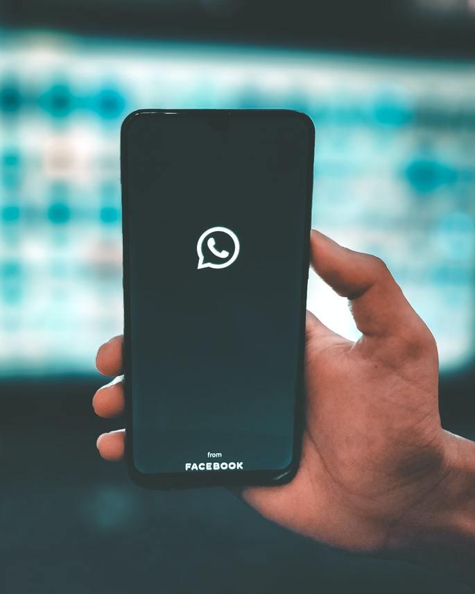 mão segura smartphone com tela inicial do WhatsApp em modo escuro