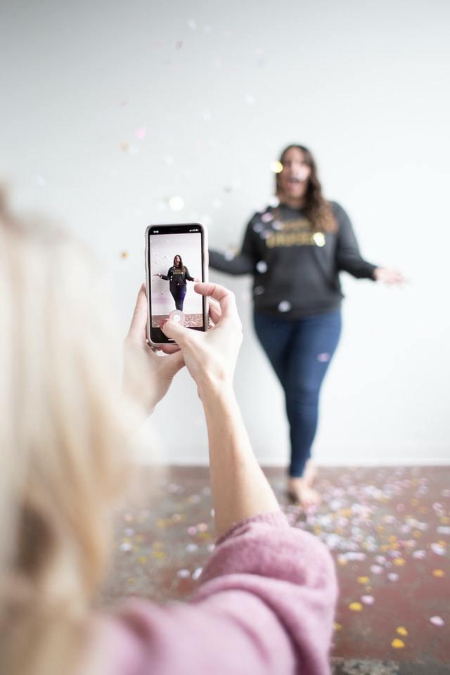 uma menina filma a outra em um cenário de chuva de papel