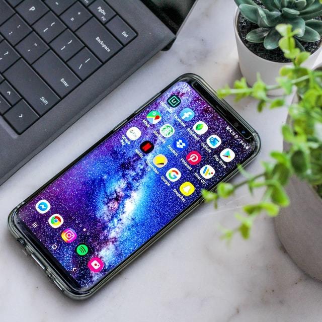 Celular Android ligado na tela inicial sobre uma mesa branca com laptop e planta ao lado