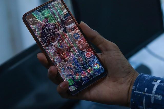 Mão segura smartphone com a tela quebrada e imagem irreconhecível