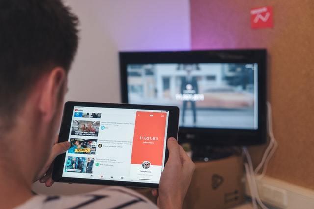 Pessoa assiste a vídeo no YouTube em tablet com outra tela ao fundo