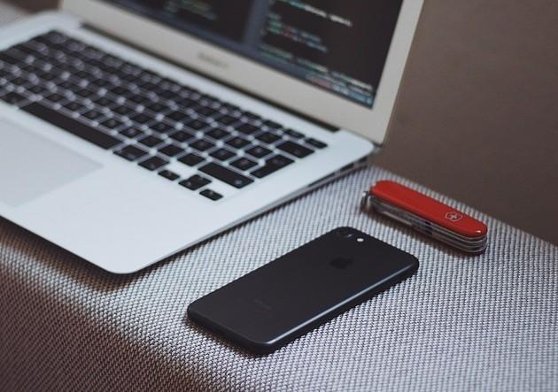 Computador ao lado de celular iPhone e canivete