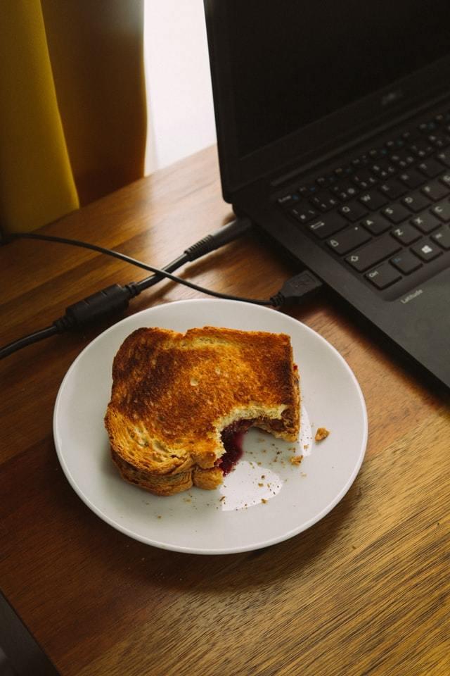 Notebook com um sanduíche mordido ao lado