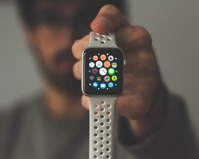 homem segura smartwatch com a tela ligada na home