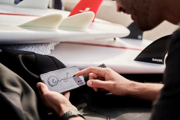 Rapaz faz assinatura eletrônica na tela do celular