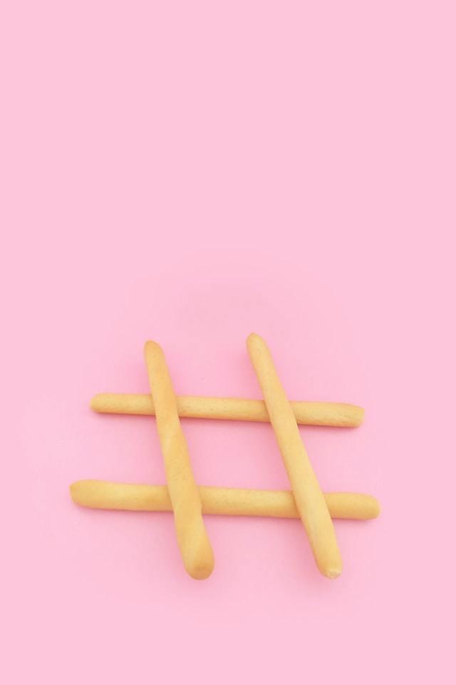 hashtag formada por palitos de biscoito em um fundo rosa