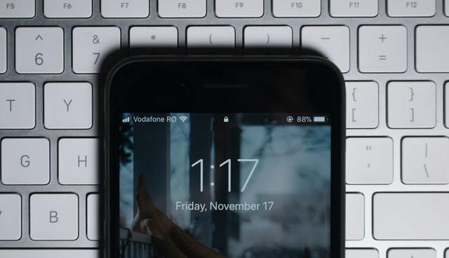 Celular preto sobre teclado branco com horario e wifi em destaque