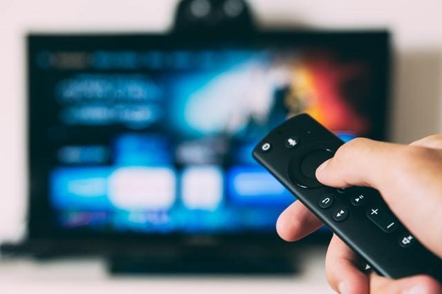 Mão segura controle de TV Box em primeiro plano e, ao fundo, há uma TV de tela plana ligada