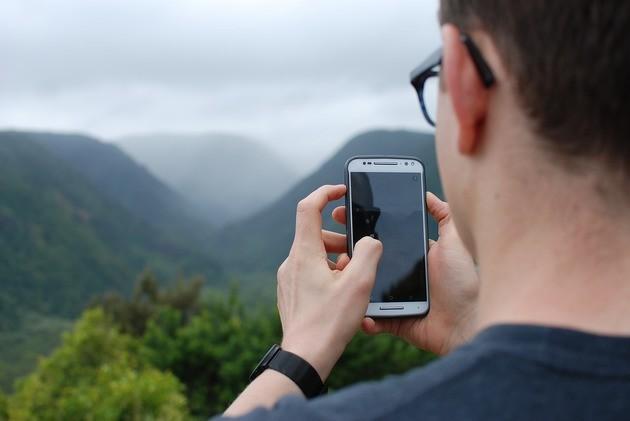 Homem com tira fotos com o celular na mão