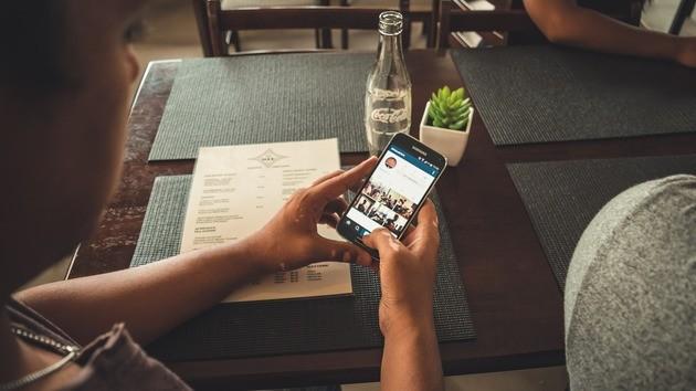 Homem no restaurante usando o Instagram