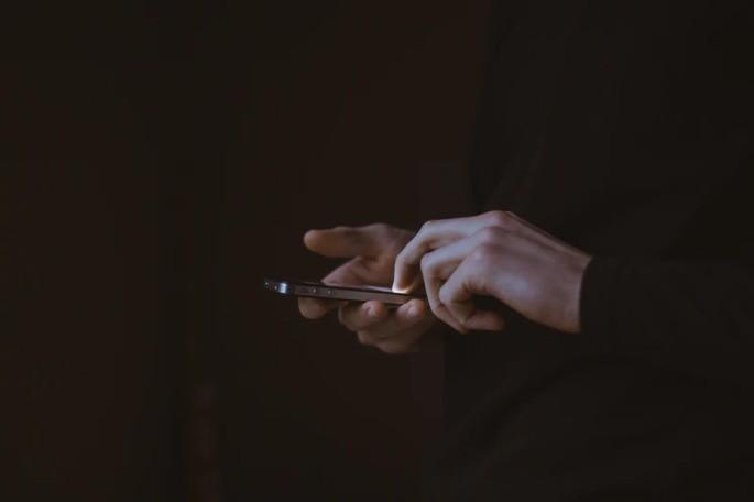mão com blusa de manga comprida preta mexe no celular em um fundo escuro
