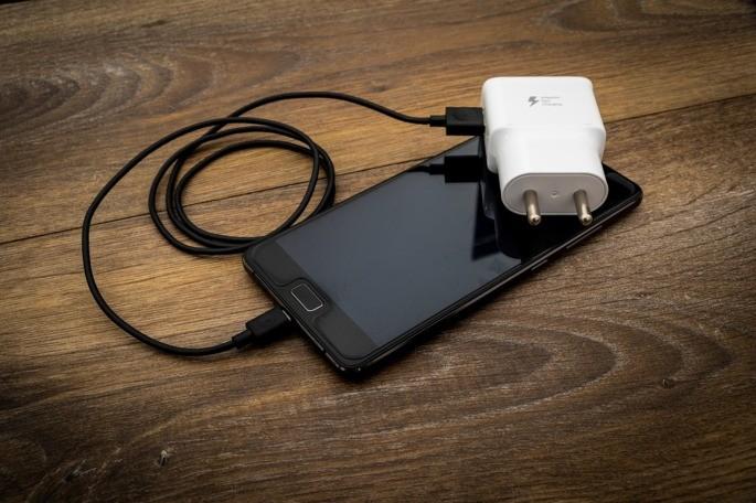 celular em cima de mesa de madeira com cabo e adaptador de tomada