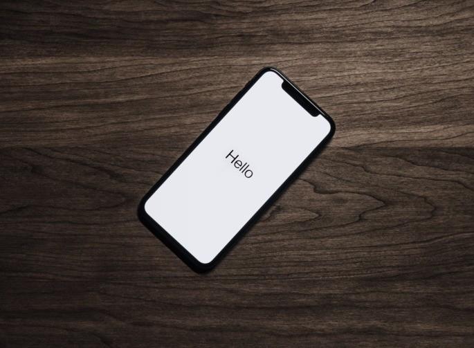smartphone em cima de mesa de madeira com tela ligada e texto Hello