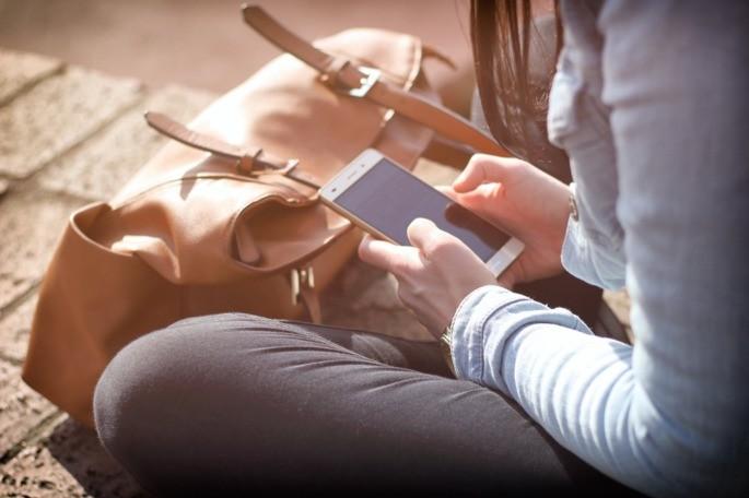 mulher de blusa social sentada no chão mexe no celular