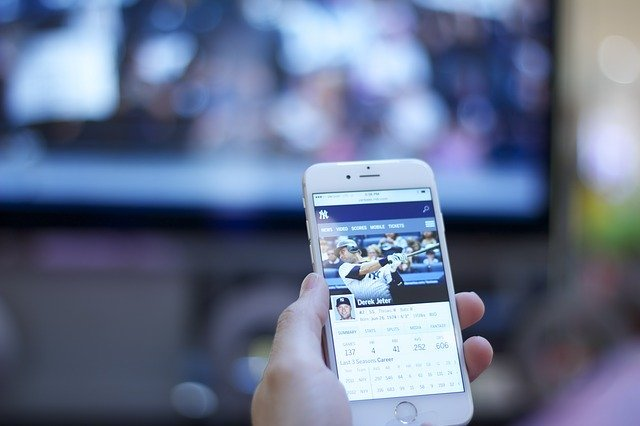 celular espelhado em tv desfocada ao fundo