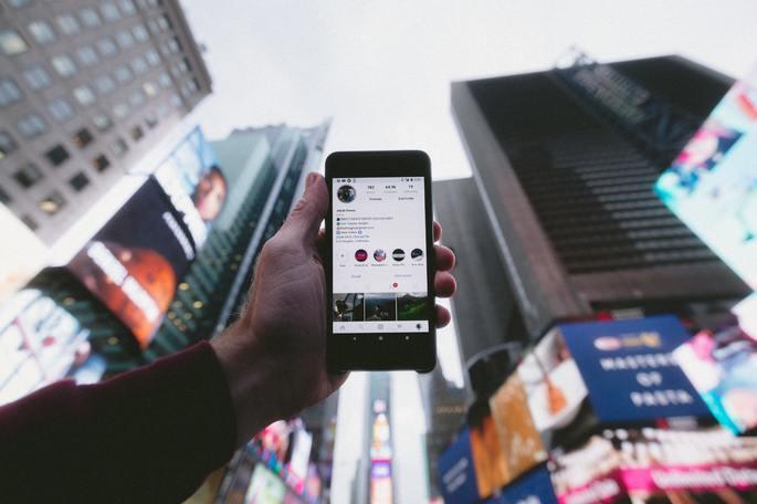 celular exibe feed do instagram em um fundo de prédios