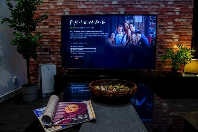 TV de tela plana exibe sinopse de episódio de Friends na Netflix em sala aconchegante