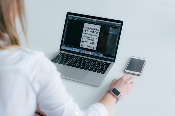mulher sentada no chão em frente à um macbook com um iphone ao lado