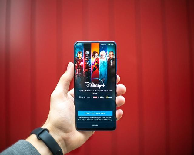 Mao segura smartphone com o app do Disney+ aberto em um fundo vermelho
