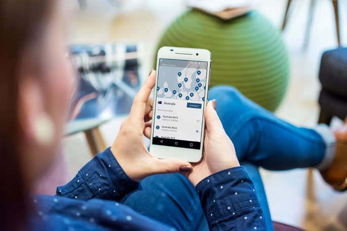 Pessoa segura o celular com VPN acessando IP da Austrália