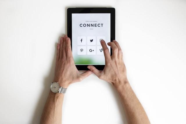 tablet em uma tela com ícone de diversas redes sociais