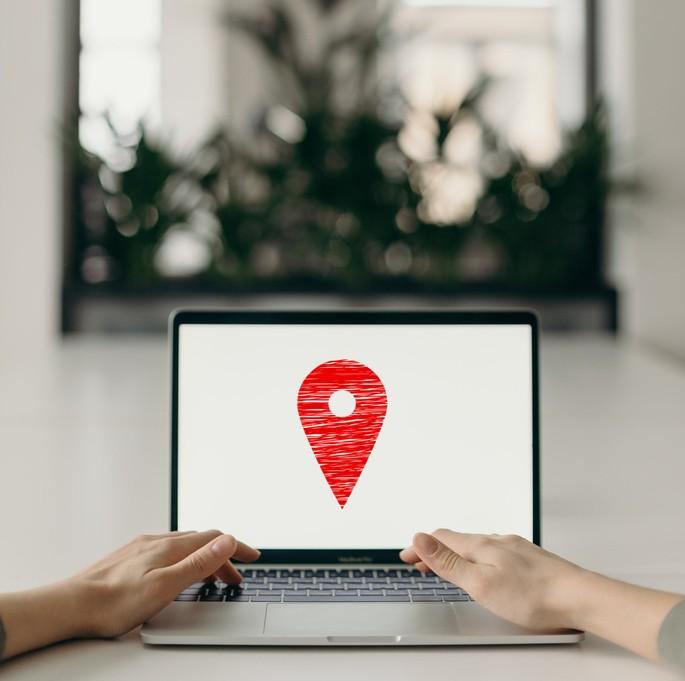 computador ligado com pin de geolocalização no centro da tela
