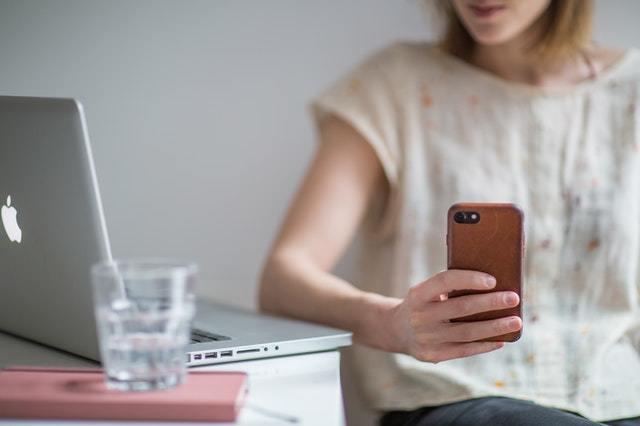 Mulher segurando um smartphone com computador na mesa e fundo desfocado