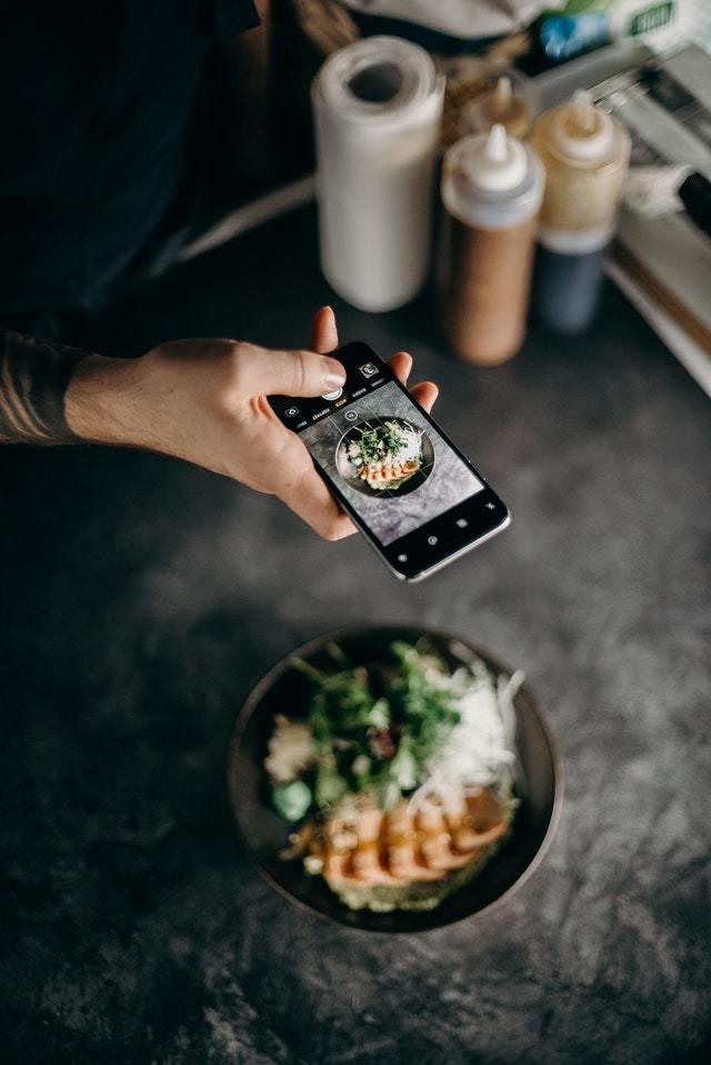 Celular tirando foto de prato de salada
