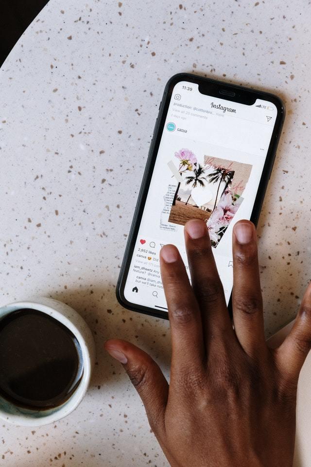 Mão curtindo post no Instagram ni smartphone com uma xícara de café ao lado