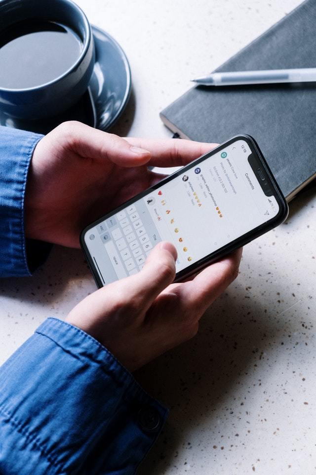 Mão segura celular sobre uma mesa. Na tela, é possível ver seção de comentários do Instagram.