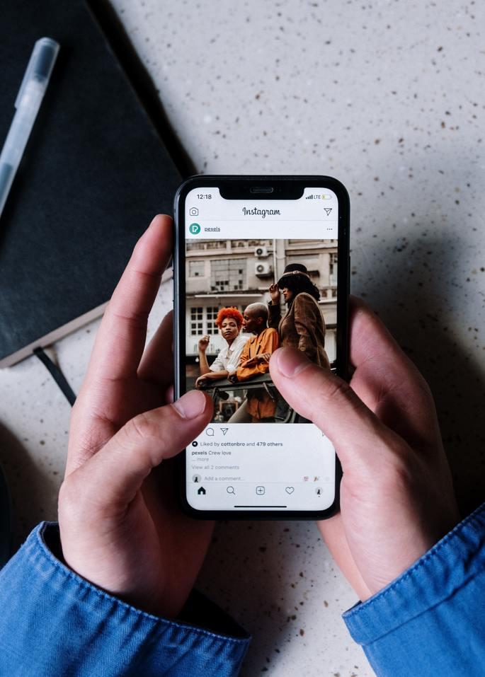 Mão segurando celular com a tela do Instagram aberta