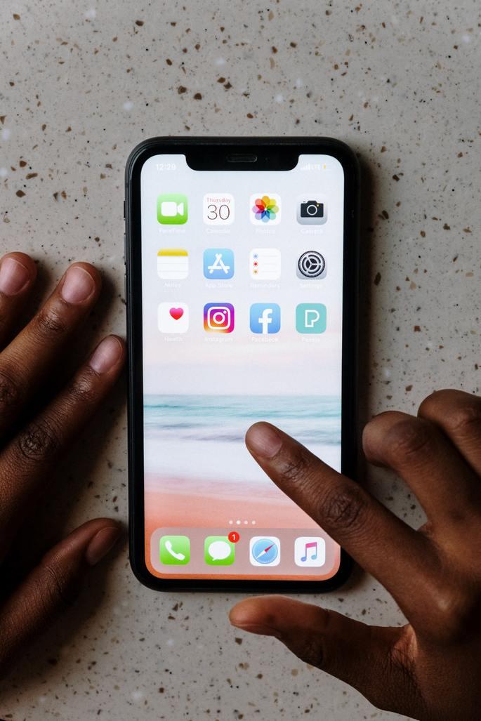 Mão mexendo na tela de apps do iPhone