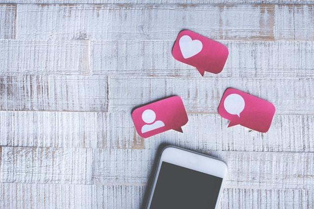 celular desligado em cima da mesa com ícones de papel do Instagram