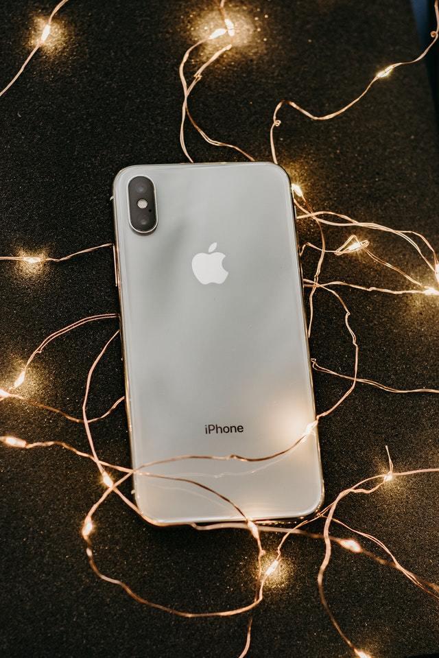 Parte de trás de um iPhone, sobre uma mesa cheia de luzes