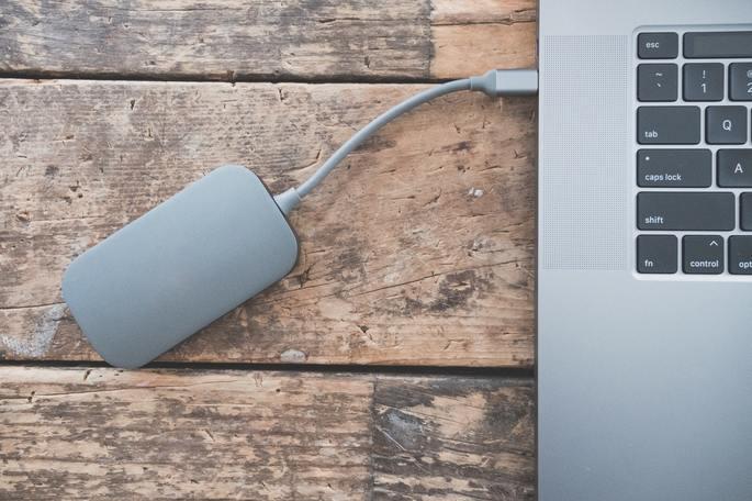 HD externo cinza ligado por cabo a laptop cinza em cima de uma mesa de madeira