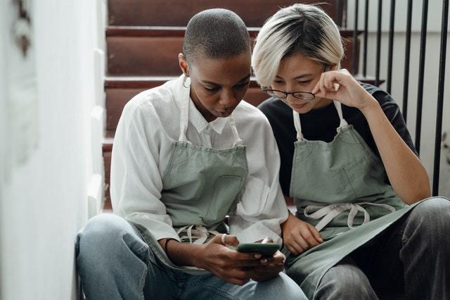 Duas mulheres olham para o mesmo celular