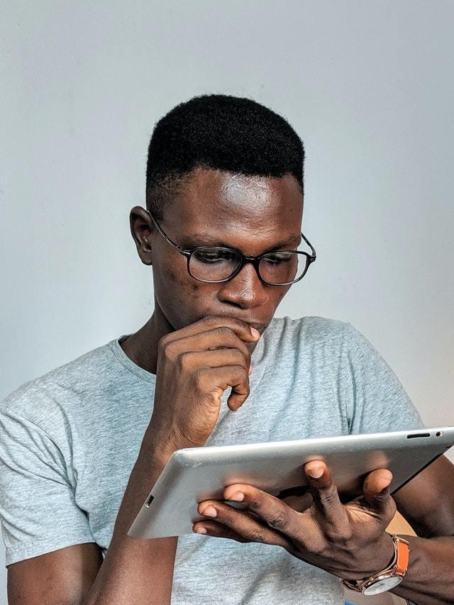 Rapaz de óculos olha concentrado para tablet