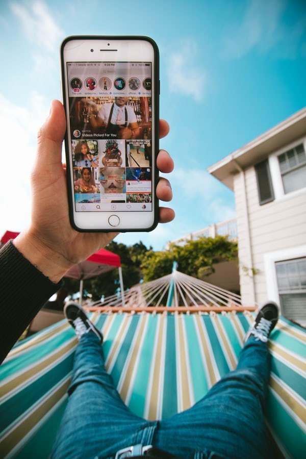 pernas de um homem deitado em uma rede vendo tela Explorar do Instagram no celular