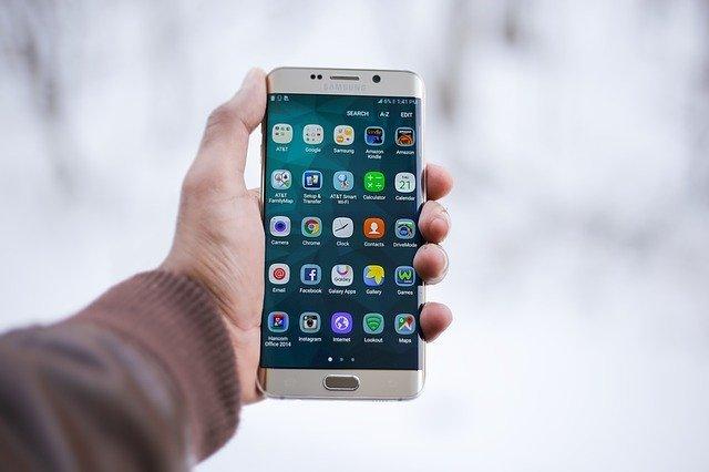 Celular segurado com fundo desfocado e tela repleta de apps