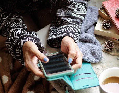 pessoa mexe em smartphone com capa verde ao lado de xícara7 de chá