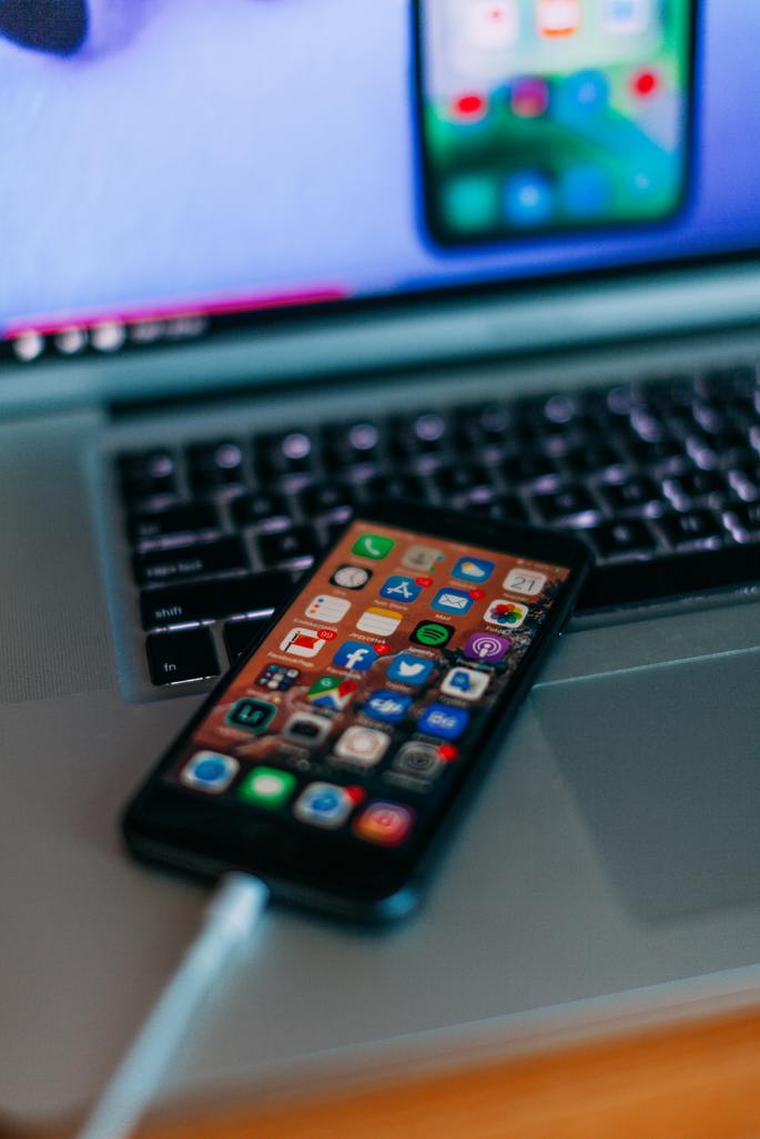iPhone ligado em cima das teclas de um laptop