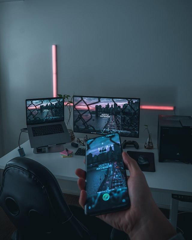 Mão segura smartphone que tem na tela a mesma imagem  exibida no computador
