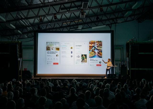 Homem faz apresentação de slide para grande público